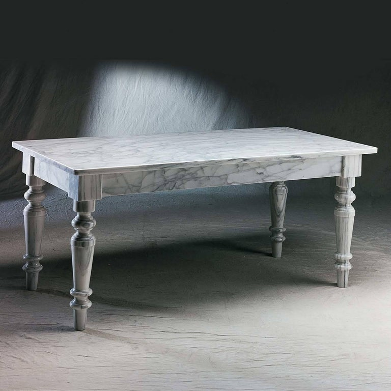 Inspired by the 19th century antique partners desk, this monochromatic single-material marble table is reinterpreted as a dining table offering ample room with a long top and tapering, fluted legs that add expansiveness to this luxurious piece. In