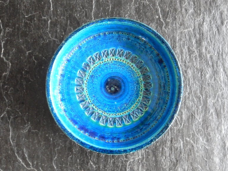 This beautiful blue ceramic bowl, from the iconic 'Rimini Blu' series, was designed by Aldo Londi for Bitossi in Italy in the 1960s. He was inspired by the colors of the sea. The decoration was engraved by hand with various recurring patterns