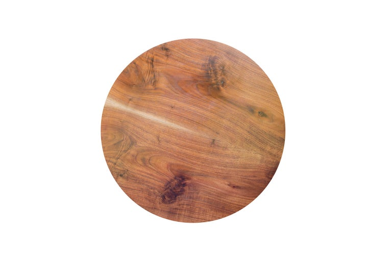The circular top on this one of a kind coffee table is a single bookmatched board of South Carolina Walnut with a subtle beveled edge and a line of pale new growth sapwood down its center. The four hand-turned and tapered legs are bound with a band