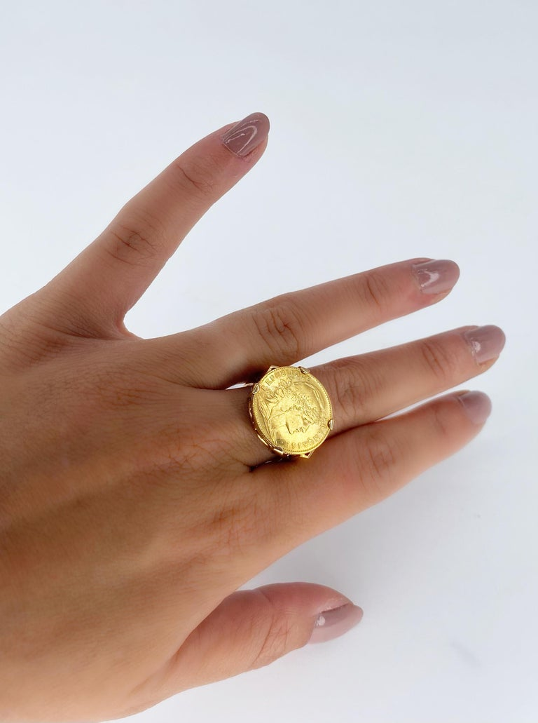 Gold coin of 20 francs mounted in ring. On the front : right profile of the Marianne wearing the phrygian cap and a crown of oak branch. Inscription : FRENCH REPUBLIC. On the reverse side the French motto : Liberty, equality, fraternity surrounds a