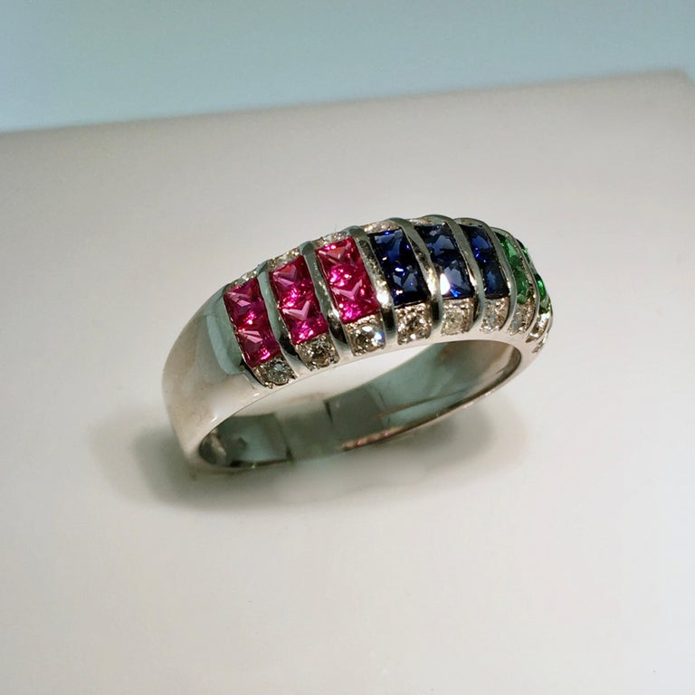 White gold ring, set with diamond, ruby, sapphire and emerald. A special band ring when it comes to the gems used. The square cut is called Princess cut. Already used in diamonds so that the brilliance of the stone increases compared to the