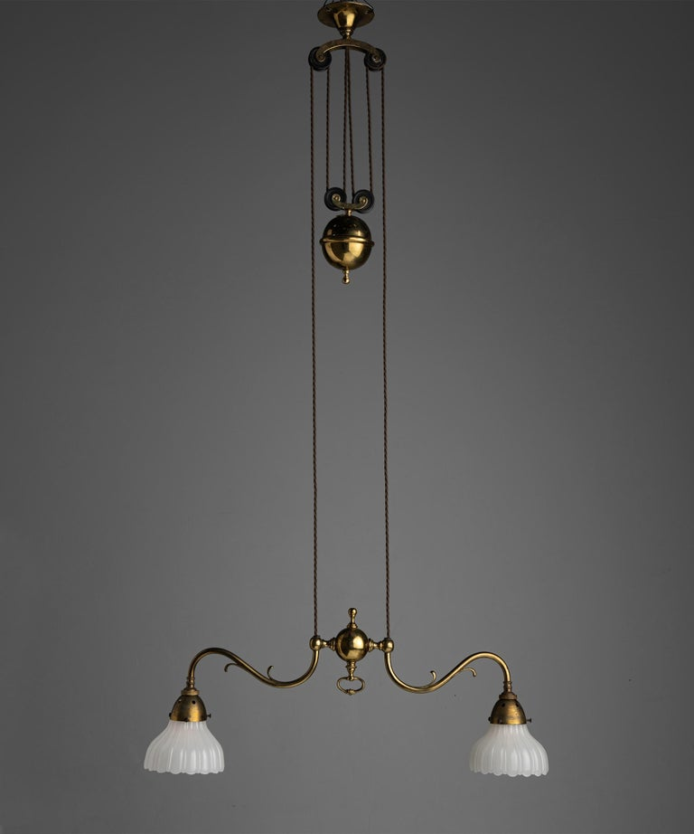 """Rise & fall gilt brass chandeliers England circa 1910  Brass framework with pulley system, and original Jefferson Moonstone Glass Shades  Measures: 27"""" W x 4"""" D x 39.5"""" H-68.5"""" H  $ 6,200 each."""