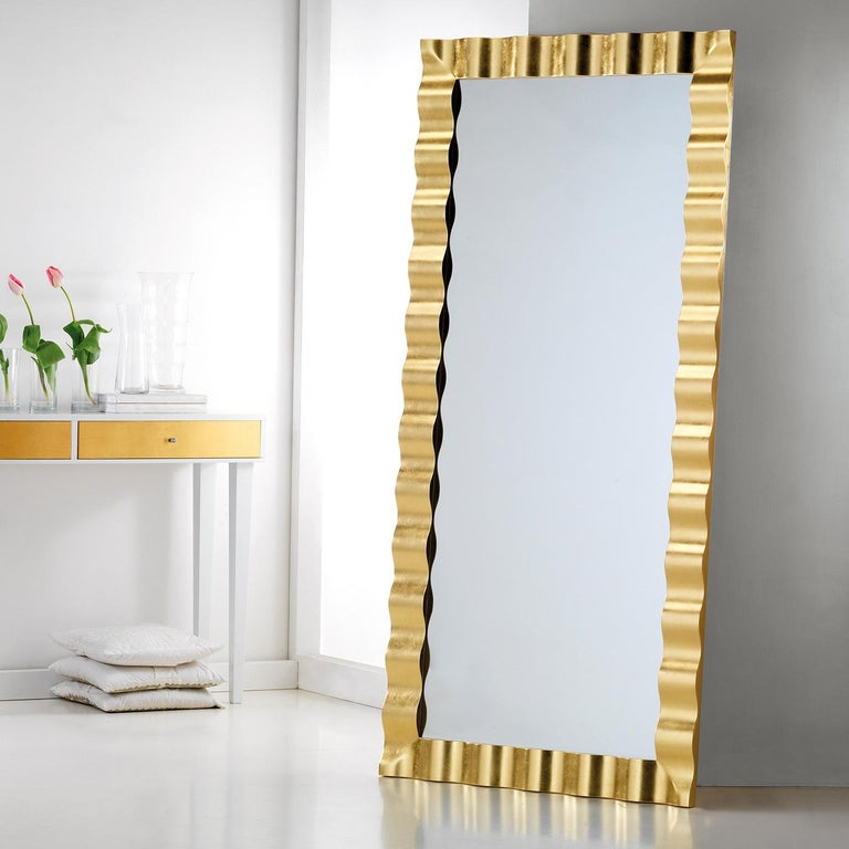 This mesmerizing wall mirror boasts a splendid wavy frame in fir wood. The 4mm-thick mirror is in prized Italian crystal, enclosed in the stunning frame (10 cm wide and 3.5 cm thick) finished by hand with gold leaf. The hooks fitted to the mirror's