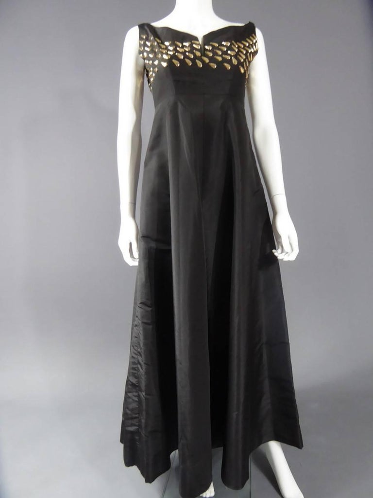 Circa 1960 France Keats model executed by Maria Carine special permission , the beautiful long evening dress in black silk taffeta, with an effect size haute.Décolté embroidered boat rhodoïd gold pellets. flared skirt ending at the ankle. Equivalent