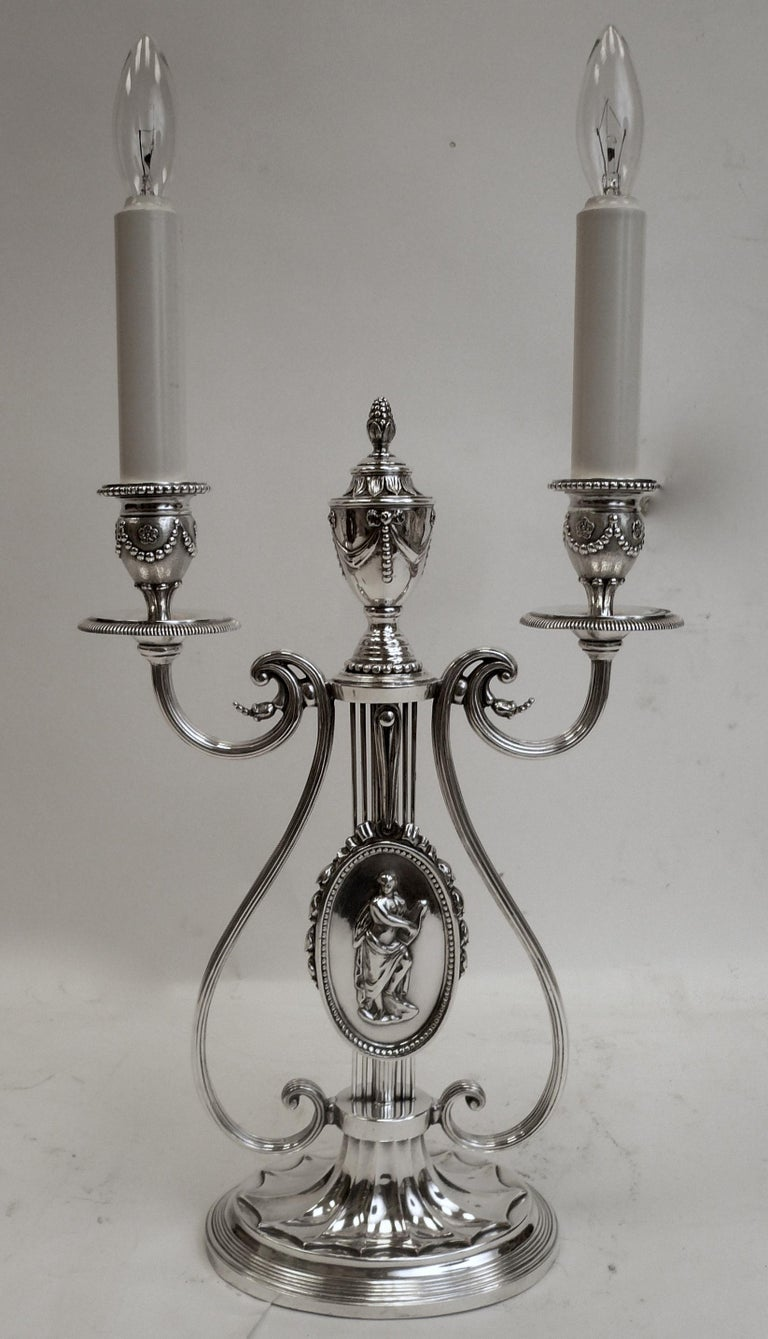 This Georgian style lyre form lamp by Caldwell features neoclassical motifs, including urns, swags, and bowknots.