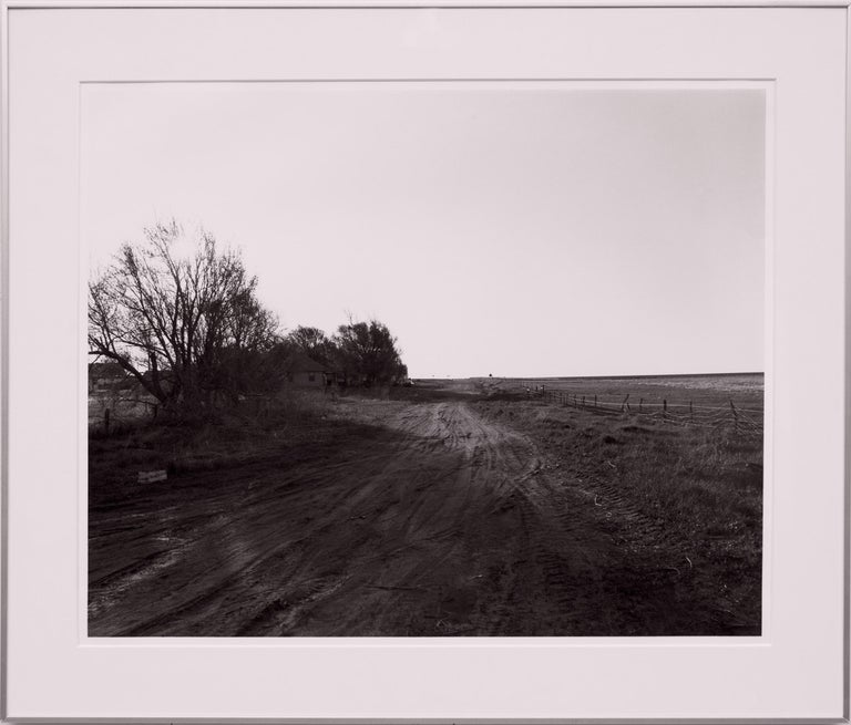 Edge of Briggsdale, Colorado, 1983 by Robert Adams (born 1937), original silver gelatin print from the Missouri West Series.  Signed, dated, numbered 2/30 and titled verso. Presented in a custom frame, outer dimensions measure 19 ¾ x 23 ¼ inches.