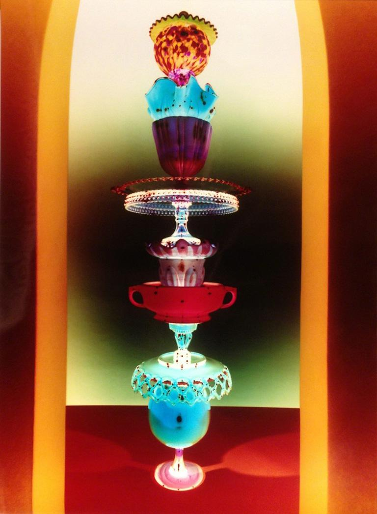 Robert Calafiore Color Photograph - Untitled - Still life tower of glass w/ jewel tone colors in yellow archway