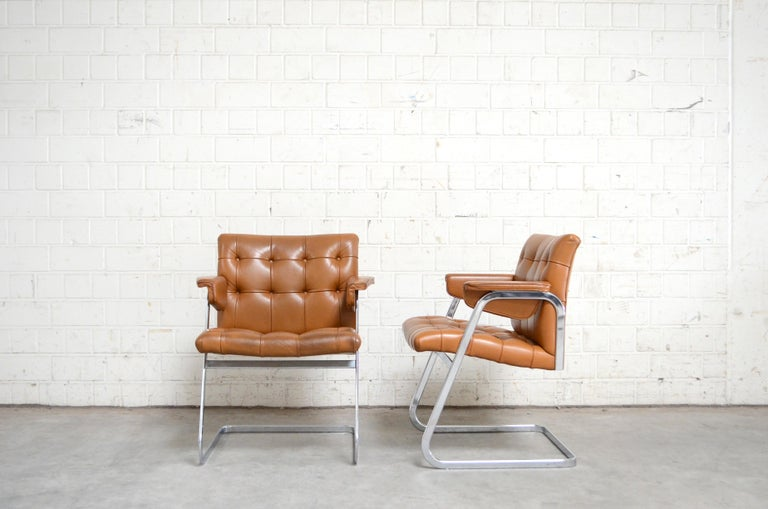 Robert Haussmann RH 305 armchairs design of 1957 and manufactured by De Sede. Brandy cognac leather. The leather was recoloured some years ago from a leather company. This version from 1970s is very rare version with Softpad armrests. The design