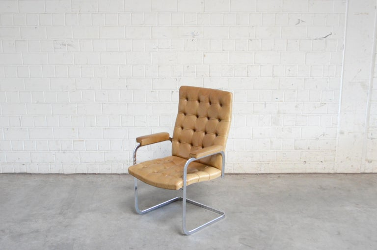 Robert Haussmann RH 305 armchair design of 1957 and manufactured by De Sede. Cognac aniline leather an a chrome steel frame. This is a Classic Swiss design chair in the tufted highback version. With some patina on the leather. Price for 1