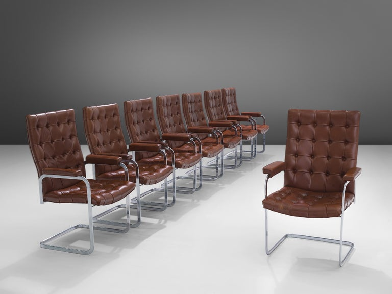 Robert Haussmann and De Sede, set of eight 'RH-304', brown leather, steel, Switzerland, 1950s  This cantilever set of tufted armchairs is designed by Robert Haussmann for De Sede. The set has a business aesthetic combined with a comfortable seat
