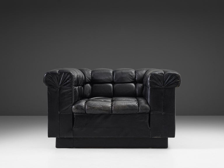 Robert Haussmann, lounge chair in leather, Switzerland, 1950s  Black leather lounge chair by Swiss designer Robert Haussmann. This easy chairs has an interesting appearance due to the expressive tufted details. The leather is separated by a