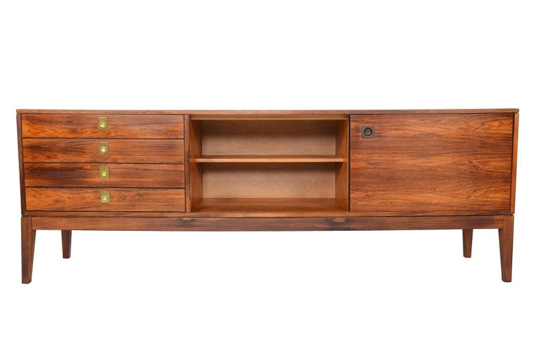 This English modern rosewood credenza by Robert Heritage for Archie Shine Furniture is a beautiful blend of traditional and modern. A bank of four drawers sit on the right of the case, each adorned with a brass flush mount ring pull. The large