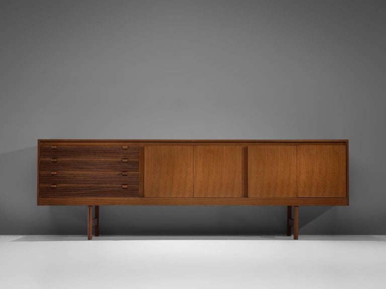 Robert Heritage for archie shine, sideboard, walnut, England, 1960s  This sideboard is equipped with a drawer section with 4 drawers and a large storage unit. The drawers are detailed with ridged fronts and wooden handles based on straight legs.
