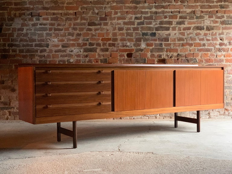 Robert Heritage Knightsbridge Model Teak sideboard credenza for Archie Shine circa 1960s, the rectangular top over four ridged drawers with angled drawer pulls, two double cupboards each with internal shelving raised on four straight