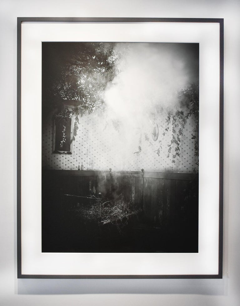 Black and white still life photograph of an old-fashioned interior filled with smoke and vines archival pigment print, edition of 10  40 x 30 inches, 49 x 39 inches in dark grey painted wood frame with 8-ply mat and non-glare glass  This