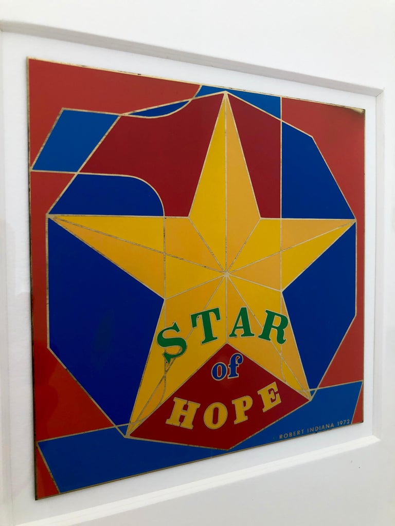 Offered is a framed in white midcentury Pop Art piece by Robert Indiana signed and dated with enamel on metal entitled,