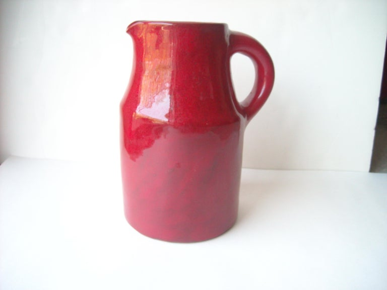 Very rare and nice pitcher for the Freres Cloutier, in a well known glaze high glossy red ceramic .the length in clouding handle is 7 1/4. Signed Cloutier R J, France.