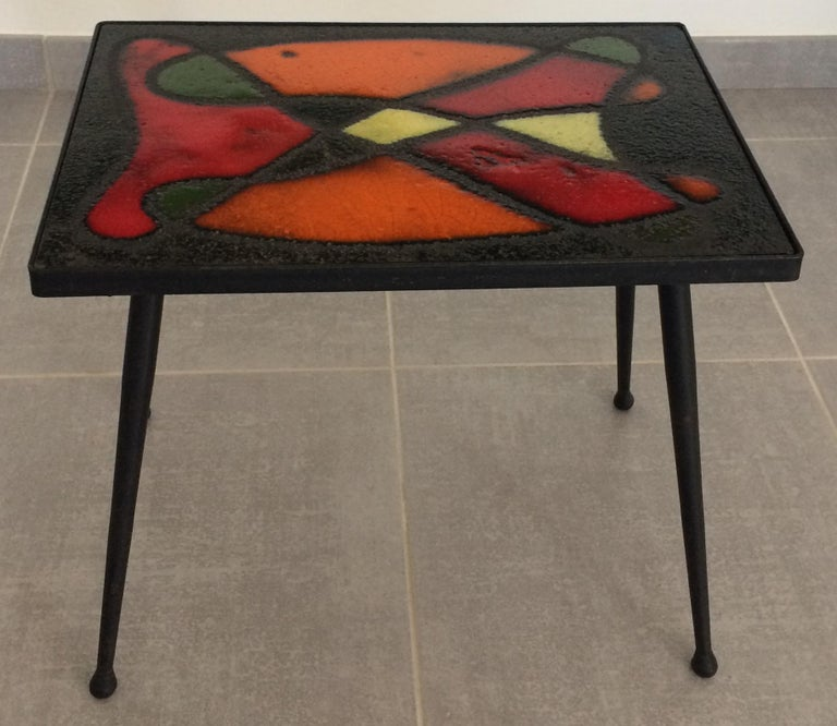 A boldly colorful glazed ceramic tile table by Jean and Robert Cloutier, circa 1960, France.  Stunning colors of hot orange, bright red, black, grassy green and pale yellow.  This table by the dynamic design duo can be converted into artwork to