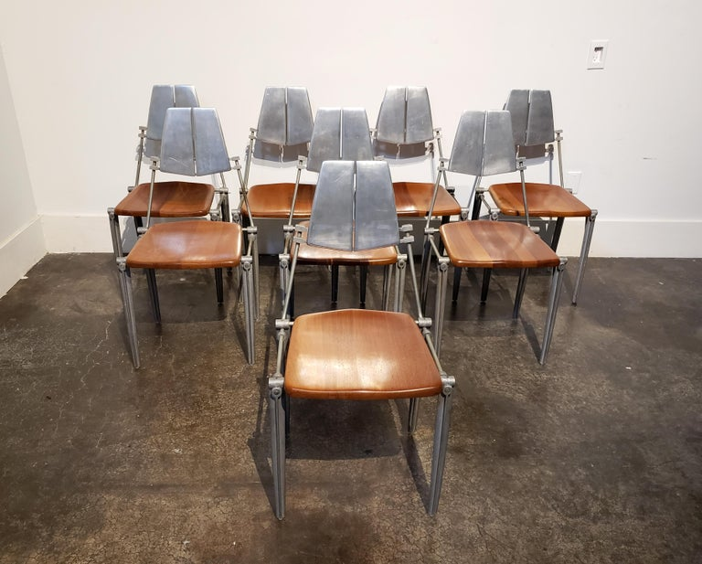 Chic, cast aluminum dining chairs with warm maple wood seats designed by Los Angeles designer and manufacturer, Robert Josten in the 1980s. Classic Josten styling with elegant curved legs and exaggerated Industrial fittings. Seat backs are polished