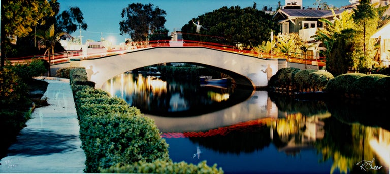 """""""Spirit Gondoliers, Venice, CA,"""" is an original fine-art photograph by Robert Kawika Sheer. The image is signed in the lower right and numbered in the lower left. The image depicts a bridge with a red railing over canal of still water that reflects"""