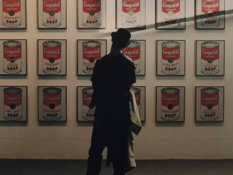 This is a singular original vintage photograph from Robert Kent Sharpe's (1930-2016) personal collection capturing a moment in time of an art observer admiring Andy Warhol's Soup Cans.  This is a series of Mr. Sharpe's human observation projects and