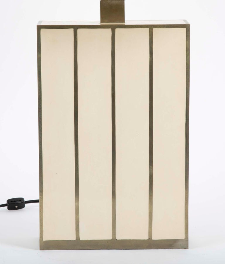 A rectangular form Robert Kuo table lamp with ivory colored panels inside brass banding. With new shade.