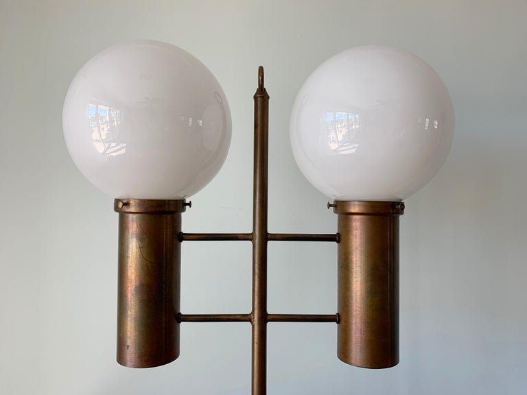 Large table lamp by Robert Long. The lamp is made from solid brass and opal glass. It features 2 sockets for the glass globes, 2 sockets for the bottom of the brass cylinders (ambient light) and a 3-way switch (top, bottom and both). Wired for use