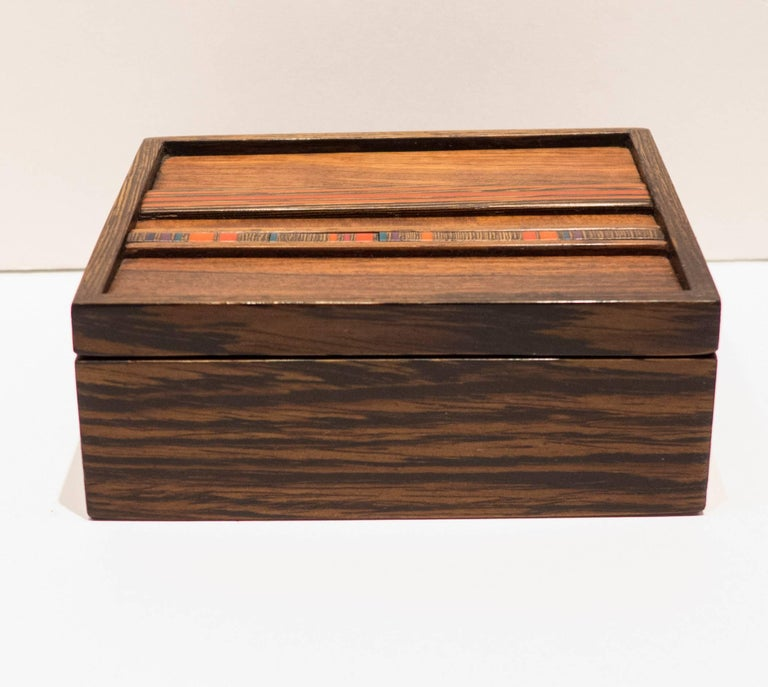 Wooden lidded box with two bands of multi-color resin inlay. By San Francisco Bay artisan Robert McKeown (1931-1989). A graduate of the California College of Arts & Crafts, McKeown was a color theorist and woodworker who won acclaim for his