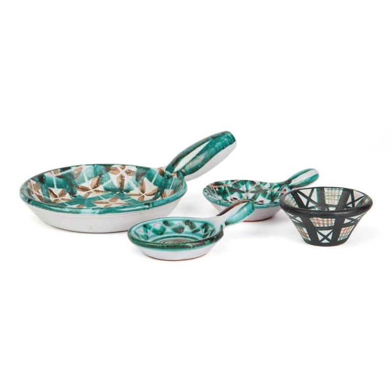 A rare and important stunning French art pottery collection of four dishes comprising a large flat and shallow handled dish with two smaller examples and a small pottery salt by Robert Picault and made in Vallauris in the South of France. Working