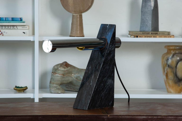 A Postmodern chrome and marble table lamp by Robert Sonneman for George Kovacs, circa 1980s. The sculptural lamp features a solid triangular shaped piece of black marble with a cantilevered chrome tube, that houses the bulb and extrudes from both