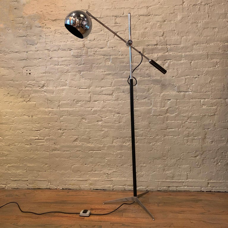 Mid-Century Modern, floor lamp by Robert Sonneman features a chrome and painted stem with tripod base and height adjustable extension arm with leather handle and eyeball shade. The stem height is 58 inches and the foot print is 20 inches. The arm