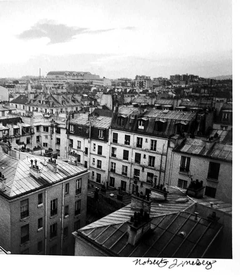 A black and white landscape photograph of the rooftops of Paris, France in the 1980s, in the 11th District near the Opera Bastille.  Paris Rooftops, 1988 by Roberta Fineberg is an 11 x 14 (sheet size) gelatin silver print. Signed and titled on image