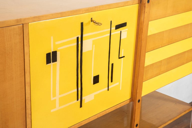 Very rare oakwood credenza designed by Roberto Aloi circa 1955, enameled steel, abstract black and yellow pattern printed plastic and glass.  Two doors conceal, two adjustable shelves and three drawers storage compartment.