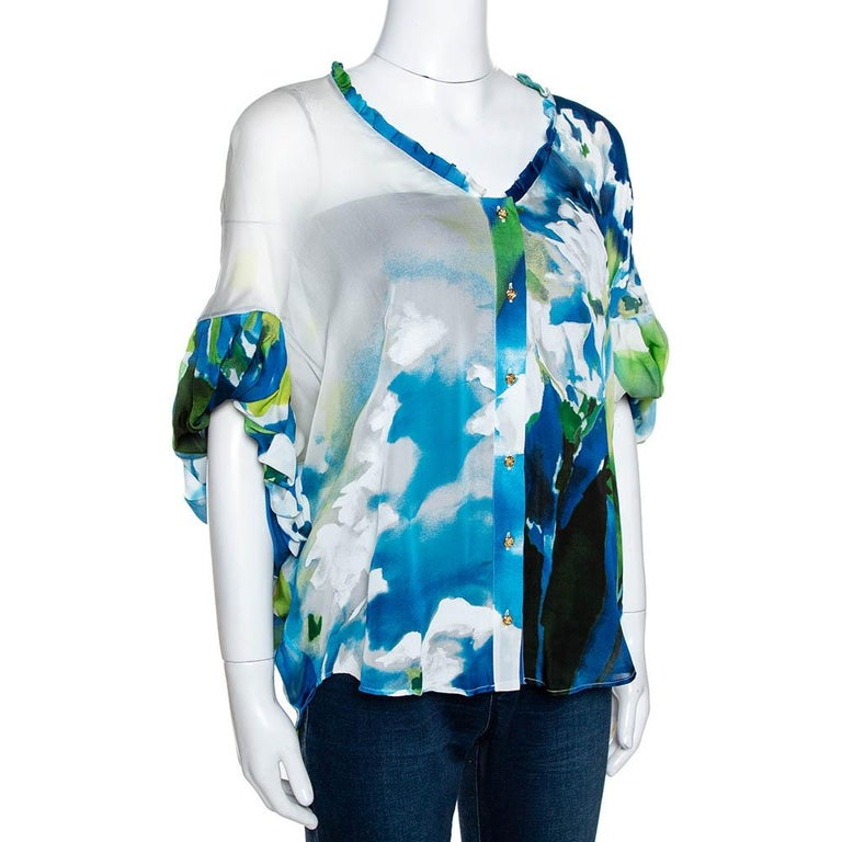 Stylish and fun, this Roberto Cavalli blouse is great for outings. It has been cut from pure silk and comes in a lovely shade of blue. It flaunts an interesting print throughout. It has gathered sleeves, a v-neck and button closure.