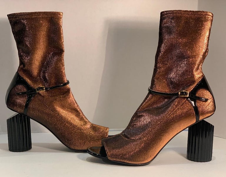 Very avant garde, Italian luxury brand, Roberto Cavalli, size 41 bootie shoes.  These edgy shoes feature open toes, a striking copper metallic slight stretch fabric with black patent leather trim, and a unique black circular fluted 4 inch high heel.
