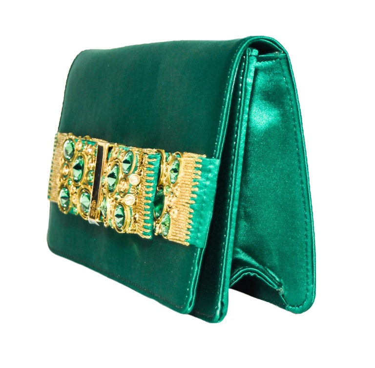 Roberto Cavalli intense green satin clutch is decorated with a green bow that has been embellished with green and gold tone beads and crystals.  The bow is located on the front flap and, for closure, a hidden magnetic snap under flap.  The interior
