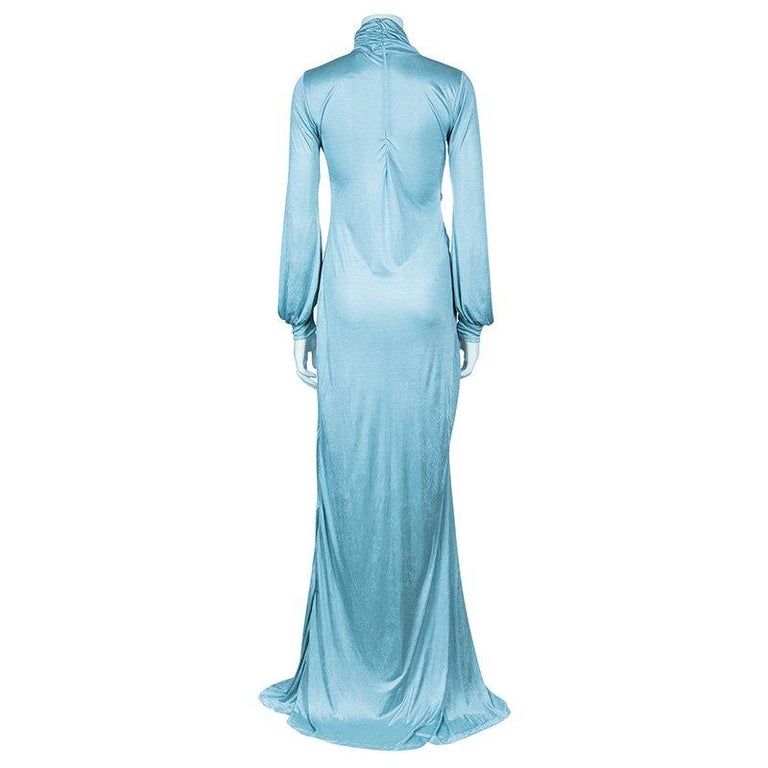 A mesmeric style awaits you in this Roberto Cavalli jersey gown. It comes crafted in 100% polyester and features draped pattern with crystal studded brooch. It has full sleeves with cuffs. A high neck and back zipper closure completes the stately