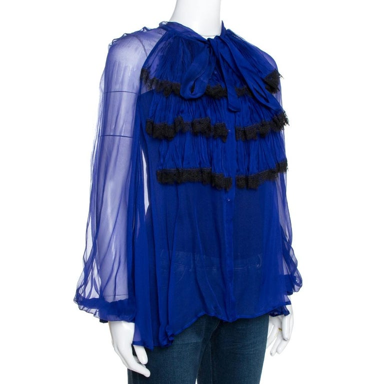 This lovely silk top is great for formal occasions. It hails from the house of Roberto Cavalli. It carries a lovely shade of royal blue and has a flattering silhouette. It is styled with long sleeves, ruffled detailing, button closure and
