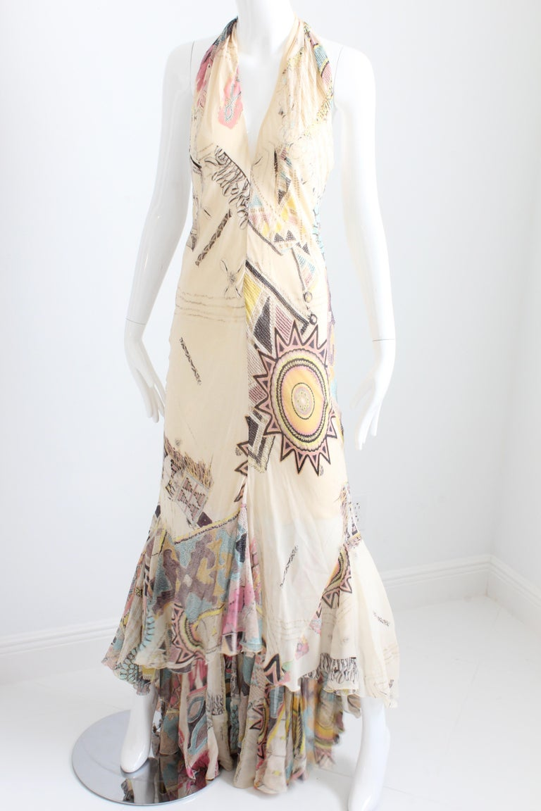 This lovely silk chiffon halter dress was made by Roberto Cavalli and previously owned by Serena Williams.  It features an abstract print with sunburst motif against a creme colored background and is partially lined to the mid-thigh.  The godet