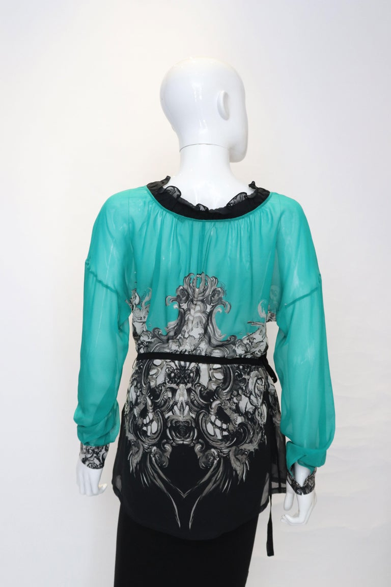 A great silk top by Roberto Cavalli. The top is emerald green and black in colour with a frill neckline and short sleeves. It has a black silk tie belt.