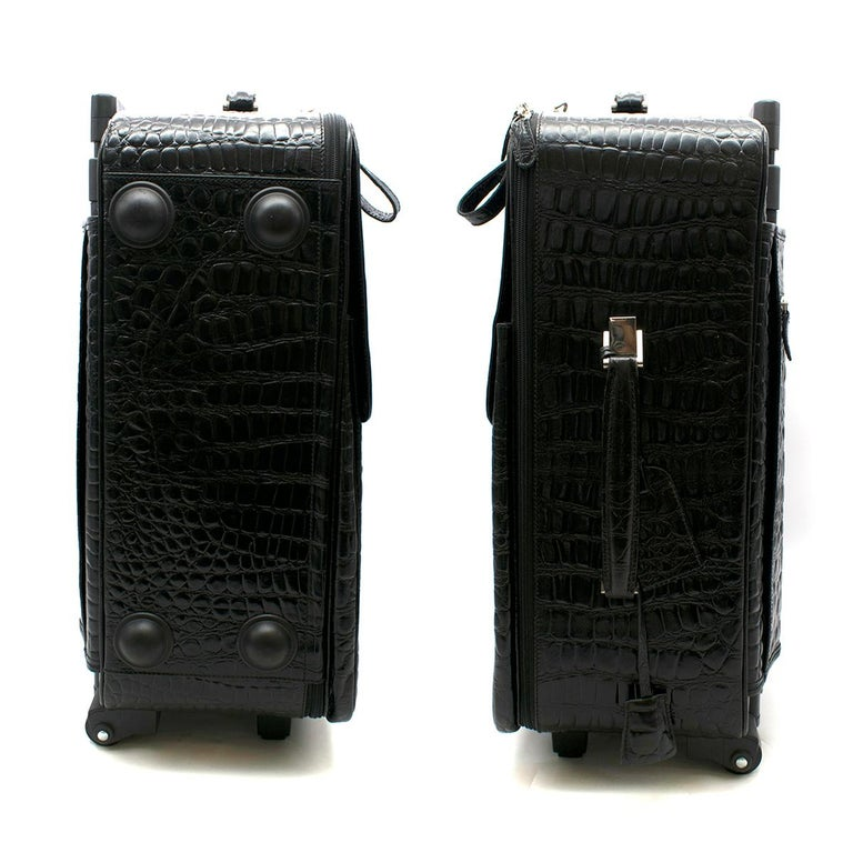 Roberto Celk Artioli Black Crocodile Carry-on Suitcase   Outer:  - Textured Crocodile leather  - Retractable handle - Side and top handle  - Wheels - Protective plastic feet on the bottom - Silver toned hardware  - Luggage tag  - Lock with keys  -