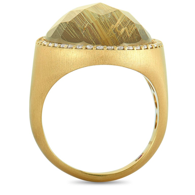 This Roberto Coin ring is crafted from 18K yellow gold and set with a 15.00 ct rutilated quartz and a total of 0.40 carats of diamonds. The ring weighs 15.3 grams, boasting band thickness of 4 mm and top height of 7 mm, while top dimensions measure