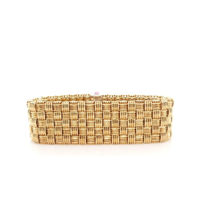 Authentic Roberto Coin 18 karat yellow gold flexible five-row woven look bracelet with a diamond-encrusted clasp from the Appassionata collection. The round brilliant cut diamonds (F-G in color, VS-SI clarity) estimated at 0.30 carats total are set