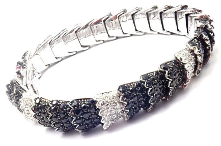18k White Gold Diamond Black Sapphire Cobra Bracelet by Roberto Coin.  With 198 round brilliant cut diamonds VS1 clarity, G color total weight approx. 5ct 528 black sapphires total weight approx. 13ct 1 Ruby Details: Weight:  46.2 grams Length: