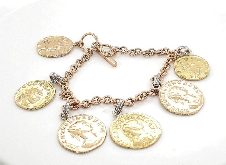 Authentic Roberto Coin charm bracelet crafted in tri-color 18 karat gold. Gold charms are set with approx. 0.30 carats of round brilliant cut diamonds (G color, VS clarity). Signed Roberto Coin 18K Italy. Roberto Coin signature ruby stone. Bracelet
