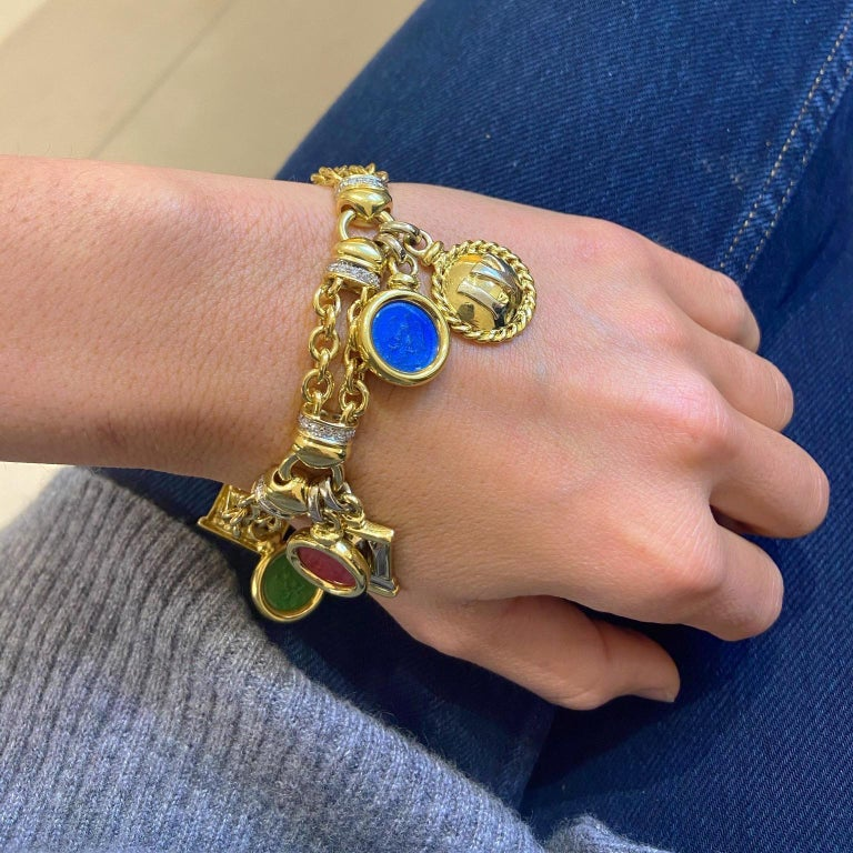 Timeless and classic charm bracelet. Designed with an 18 karat yellow gold and diamond link chain .The charms include 4 enameled peso's coin charms , along with important European and American hallmarks. The bracelet measures 7.25