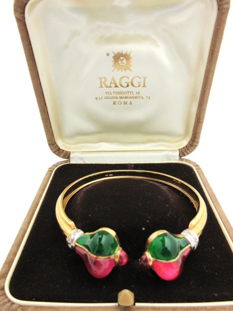 This fabulous cuff by Italian Designer Roberto Legnazzi is quite the statement piece!  Crafted from 18k yellow gold, the cuff's terminals are comprised of synthetic quartz stones in green and pink, expertly carved to fit within.  The cuff is further