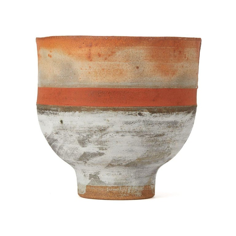 A vintage British studio pottery stoneware footed bowl by Robin Welch. The rounded bowl stands on a narrow rounded foot, the rim with opposing incisions and is glazed with an orange band with buff and grey ashen glazes above and below. The bowl is