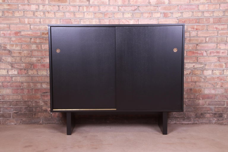An exceptional Mid-Century Modern sliding door gentleman's chest  By T.H. Robsjohn-Gibbings for Widdicomb (Retailed by John Stuart, Inc.)  USA, 1950s  Black lacquered walnut, with original brass hardware.  Measures: 51.5