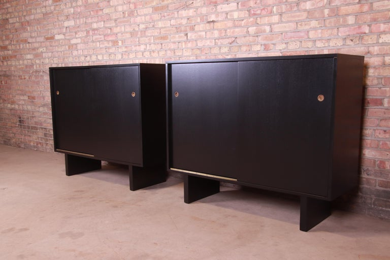 An exceptional pair of Mid-Century Modern sliding door gentleman's chests  By T.H. Robsjohn-Gibbings for Widdicomb (Retailed by John Stuart, Inc.)  USA, 1950s  Black lacquered walnut, with original brass hardware.  Measures: 51.5
